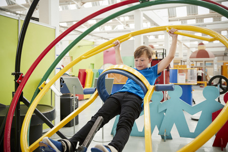 Young white boy in science centre using human gyroscope