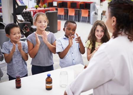 Classmates applauding teacher after a science experiment