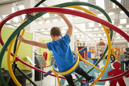 Young white boy using human gyroscope, back view Stock Photo