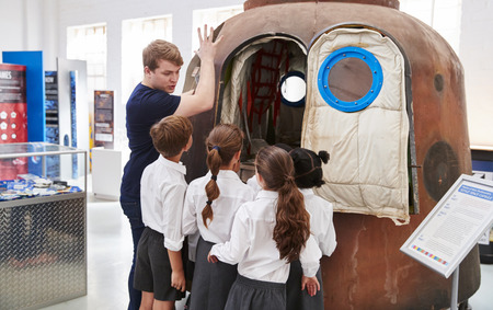 Kids and teacher look at a space capsule at a science centre Stock Photo