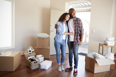 Happy Couple Surrounded By Boxes In New Home On Moving Day Stock fotó