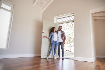 Couple Opening Door And Walking In Empty Lounge Of New Home Standard-Bild