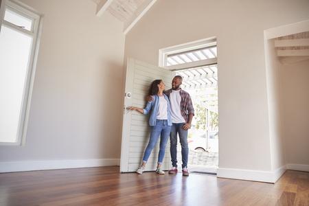 Paar, das Tür öffnet und in der leeren Lounge des neuen Hauses geht Standard-Bild