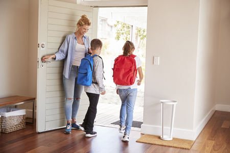 Mother Getting Children Ready To Leave House For School Stockfoto