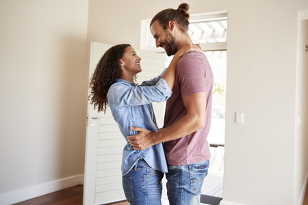 Excited Couple Hugging By Open Front Door In Lounge Of New Home