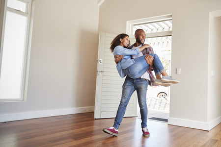 Man Carrying Woman Over Threshold Of Doorway In New Home Stockfoto