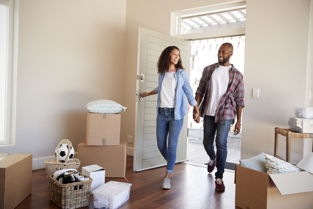 Couple Holding Hands Walk Into New Home On Moving Day