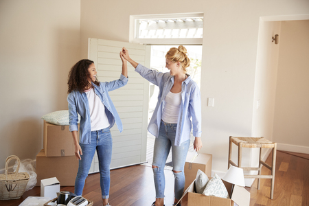 Female Friends Celebrating In New Home On Moving Day