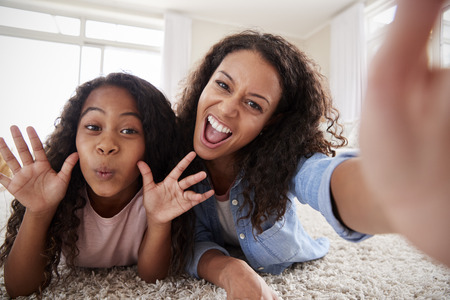 Mother And Daughter Lying On Rug And Posing For Selfie At Home Stock Photo