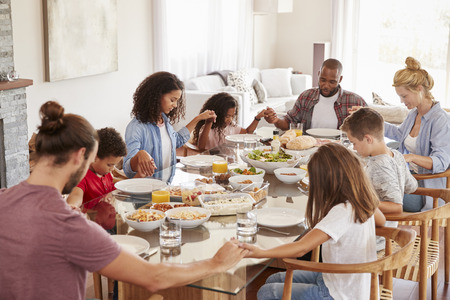 Two Families Praying Before Enjoying Meal At Home Together