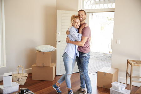 Happy Couple Surrounded By Boxes In New Home On Moving Day Stok Fotoğraf