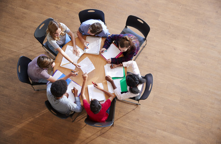 Overhead Shot Of High School Pupils In Group Study Around Tables