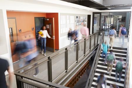 Corridoio occupato del liceo durante la ricreazione con studenti e personale offuscati