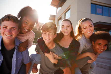 Portrait Of High School Students Giving Each Other Piggybacks College Buildings Stok Fotoğraf - 104018479