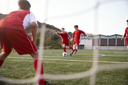 grupo de estudiantes de secundaria masculino jugando en el equipo de fútbol