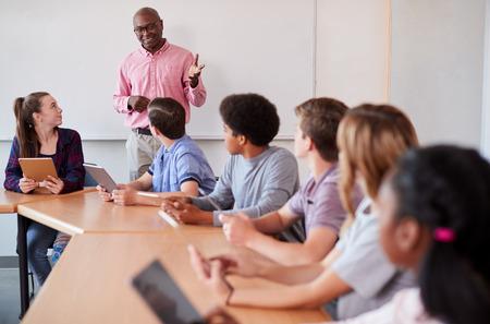 High School Teacher With Pupils Using Digital Tablets In Technology Class