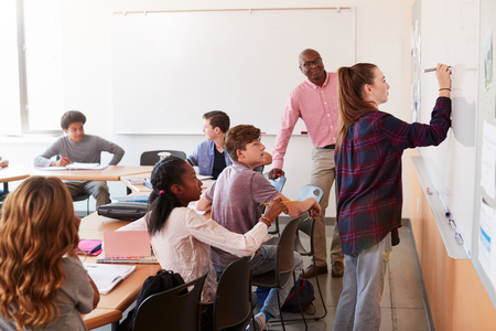 Female High School Pupil Writing On Whiteboard In Class