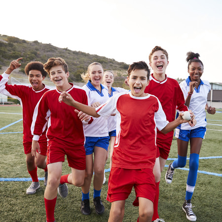 Portrait Of Male And Female High School Soccer Teams Celebrating Stockfoto