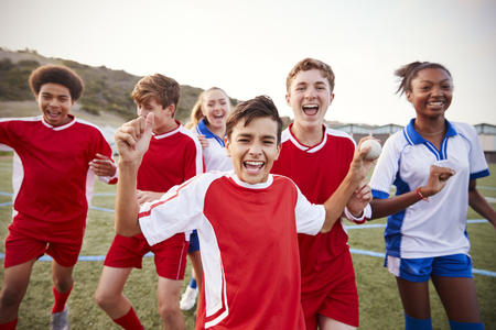 Portrait Of Male And Female High School Soccer Teams Celebrating Stock Photo
