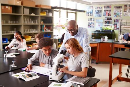Middelbare scholieren met tutor met behulp van Microscoop in biologie klasse