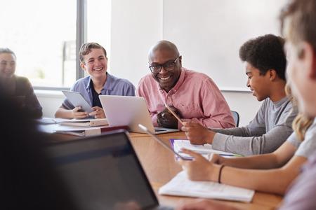 High School Teacher Talking To Pupils Using Digital Devices In Technology Class Reklamní fotografie