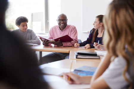 Male High School Tutor Sitting With Students At Desk In Class