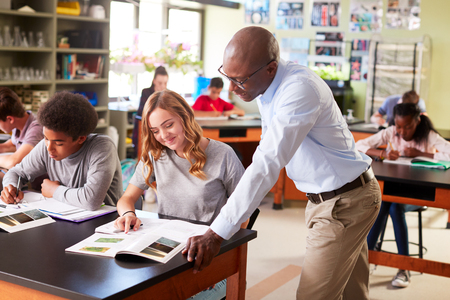 Male High School Tutor Teaching Students In Biology Class