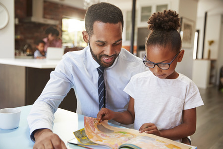 Father Reading Book With Daughter Before Going To Work