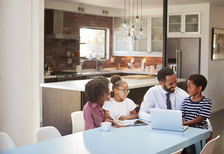 Parents Sitting Around Table At Home Helping Children With Homework