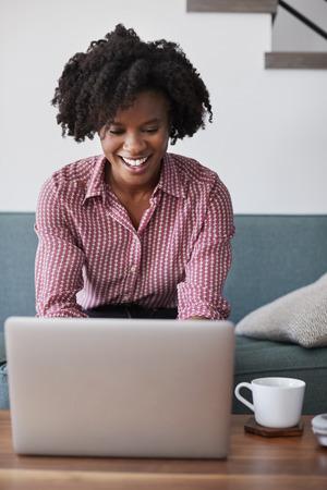 Woman Sitting On Sofa At Home Using Laptop Computer Reklamní fotografie