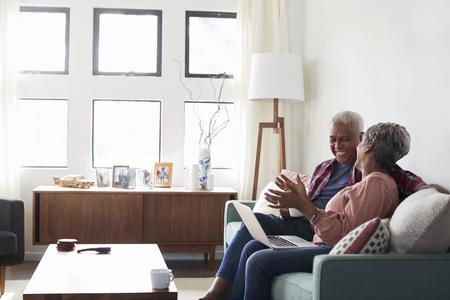Senior Couple Sitting On Sofa At Home Using Laptop To Shop Online Reklamní fotografie