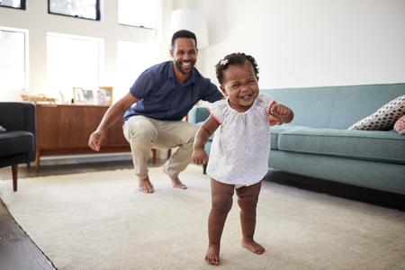 Bébé fille danse avec père dans le salon à la maison