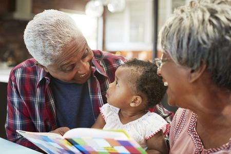 Livre de lecture des grands-parents avec petite-fille bébé à la maison