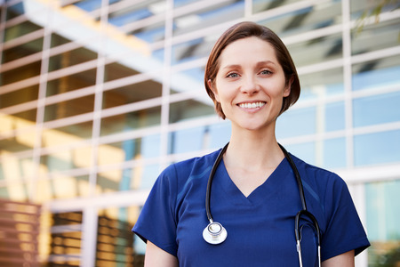Smiling white female healthcare worker outdoors, portrait