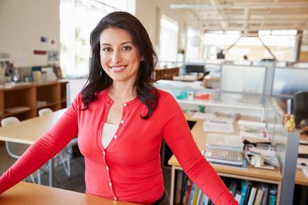Female architect smiling to camera in open plan office Stock Photo