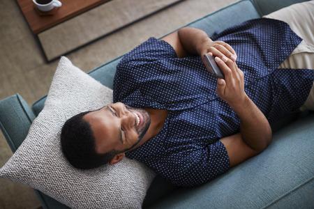 Bovenaanzicht Van Man Liggen Op Bank Thuis Met Behulp Van Mobiele Telefoon Stockfoto