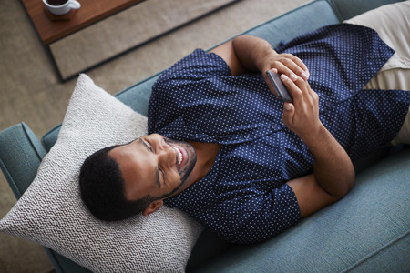 Overhead View Of Man Lying On Sofa At Home Using Mobile Phone
