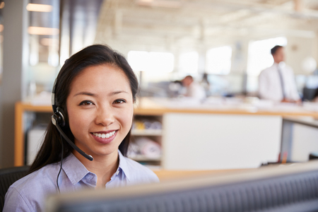 Young Asian woman working in a call centre smiling to camera