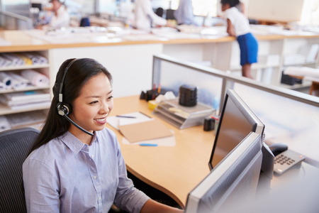 Smiling Asian woman working in a call centre, elevated view