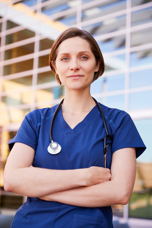 Smiling white female healthcare worker outdoors, vertical Imagens