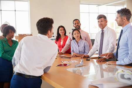 Business team stand at a meeting around a table in an office