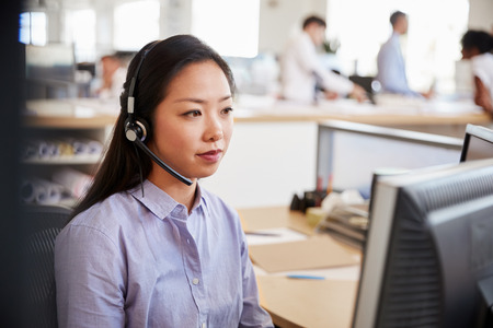Jeune femme asiatique travaillant dans un centre d'appels
