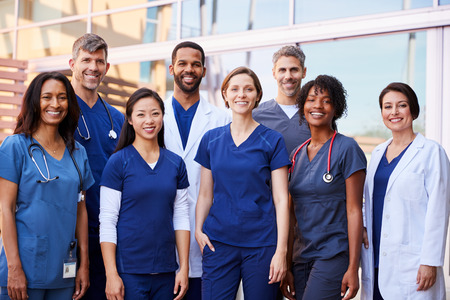 Smiling medical team standing together outside a hospital Stock Photo - 105264617