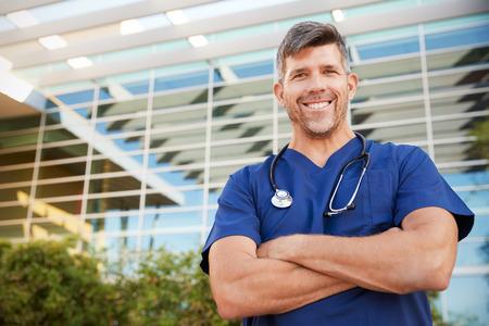 Glücklicher männlicher Gesundheitspersonal, der zur Kamera draußen lächelt