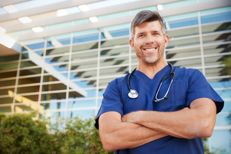 Happy male healthcare worker smiling to camera outdoors Banco de Imagens