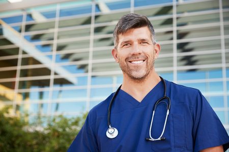 Smiling male healthcare worker outside hospital, portrait Banco de Imagens