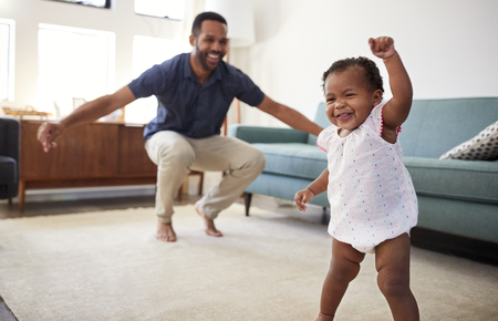 Baby Daughter Dancing With Father In Lounge At Home