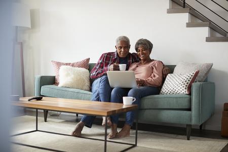 Älteres Paar, das zu Hause auf dem Sofa sitzt und Laptop verwendet, um online einzukaufen Standard-Bild