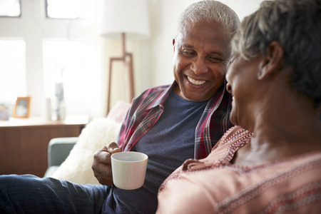 Senior Couple Sitting On Sofa At Home Relaxing With Hot Drink