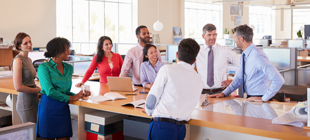 Businessman addressing team in open plan office, panoramic
